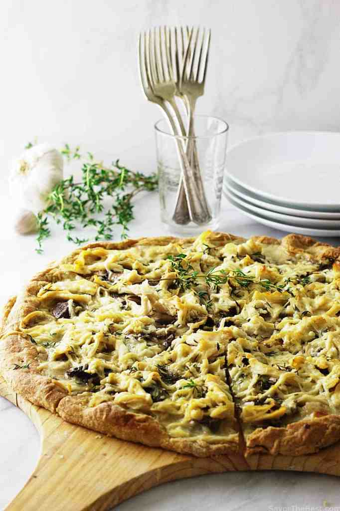 A crunchy whole grain pizza crust topped with creamy cheese sauce, fresh herbs, mushroom slices, shredded chicken and parmesan cheese.