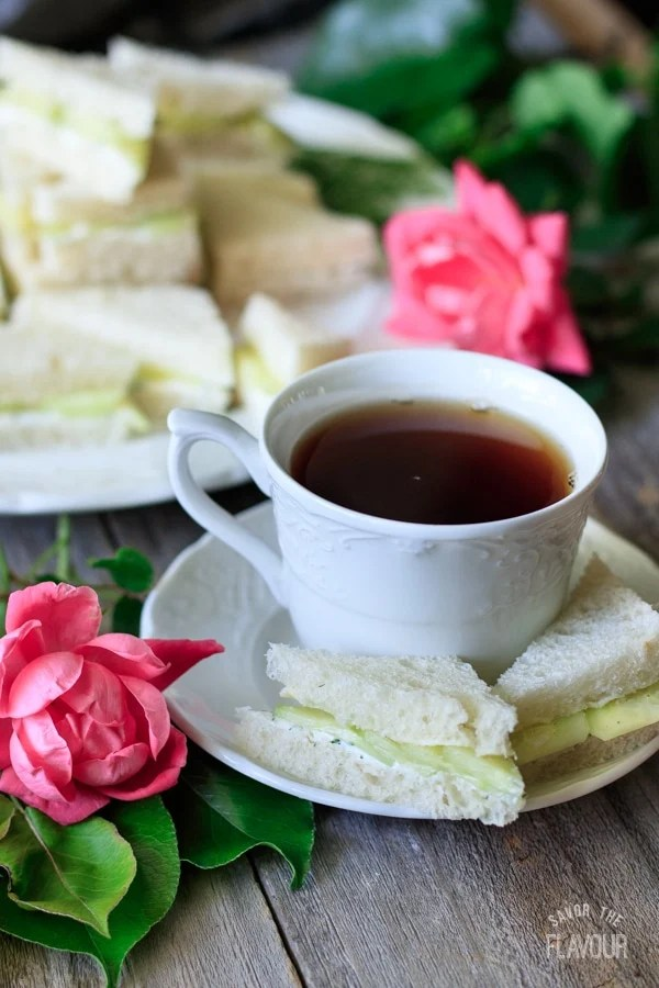 White teacup and saucer with cucumber sandwiches