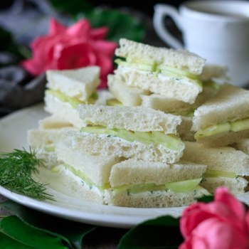 Cucumber sandwiches on a white plate with a teacup