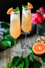 two drinks with a vase of roses and half an orange