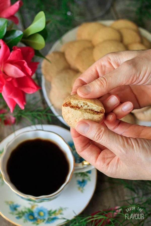 person breaking a gluten free ratafia biscuit in half