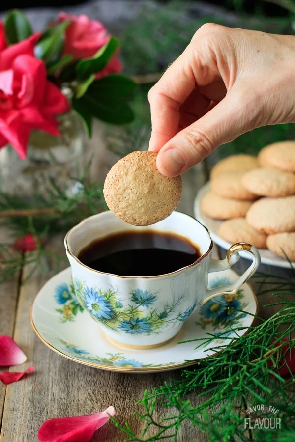 person dunking a gluten free ratafia biscuit in a cup of coffee