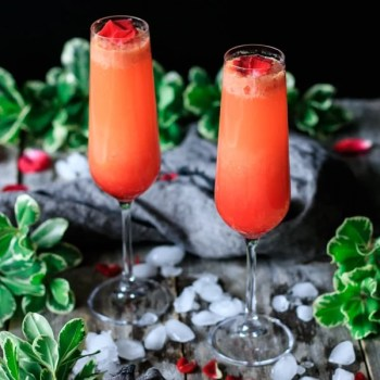 two strawberry citrus blush drinks with greenery, crushed ice, and rose petals