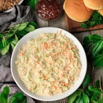 bowl of creamy coleslaw with hamburger buns, barbecue sauce, and pulled pork