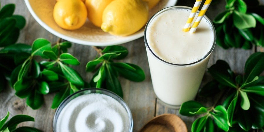 glass of frozen lemonade with sugar, lemons, and a wooden spoon