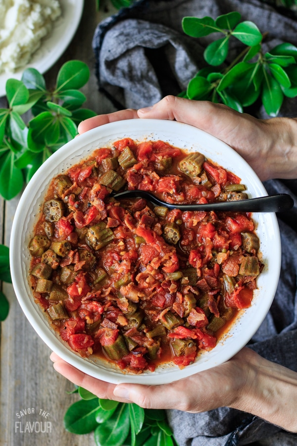person holding a white bowl of skillet Southern okra and tomatoes