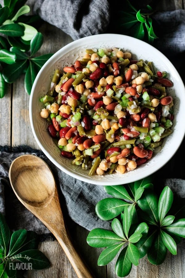 bowl of three bean salad with a wooden spoon