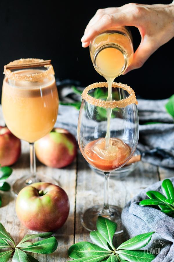 pouring apple cider to make a caramel apple mocktail
