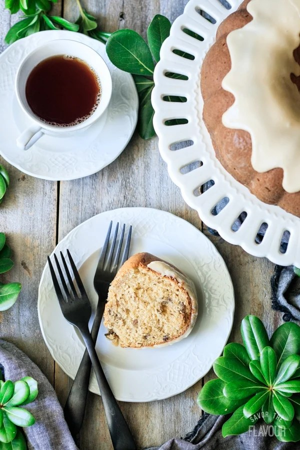 slice of maple walnut bundt cake on a plate with a cup of tea