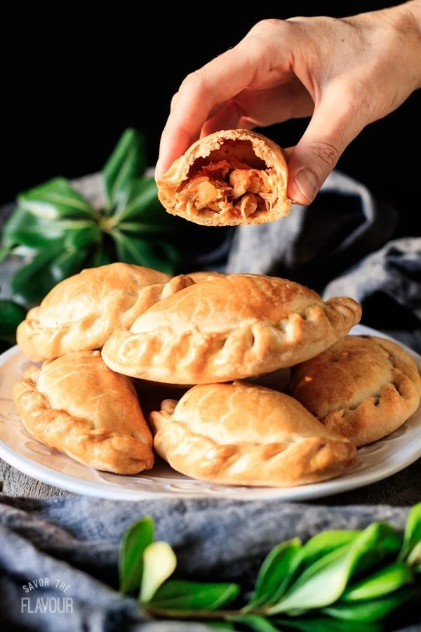 holding one of the baked chicken empanadas cut in half