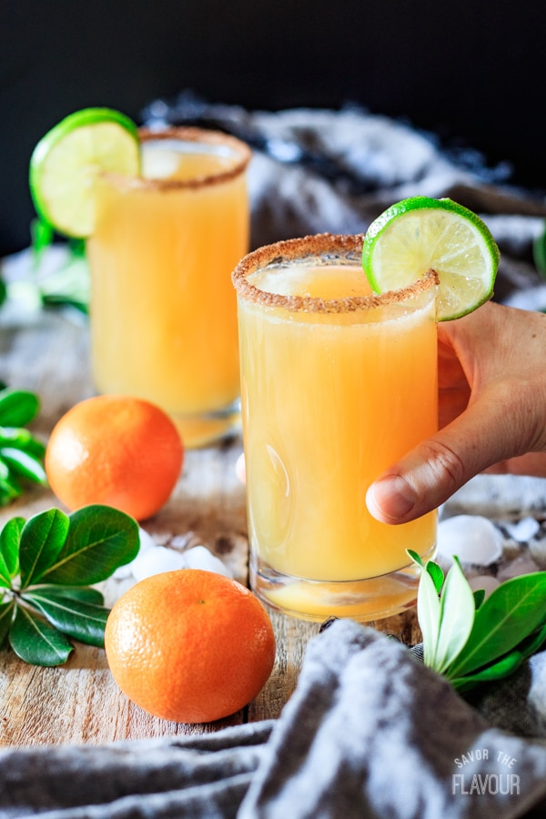 holding a glass of ginger beer mocktail with lime