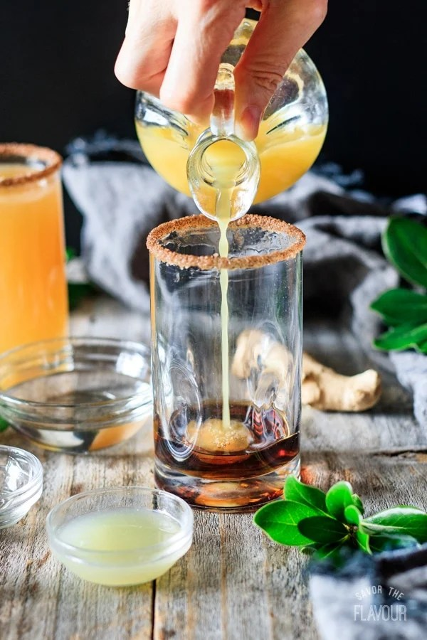 pouring orange juice into ginger beer mocktail with lime