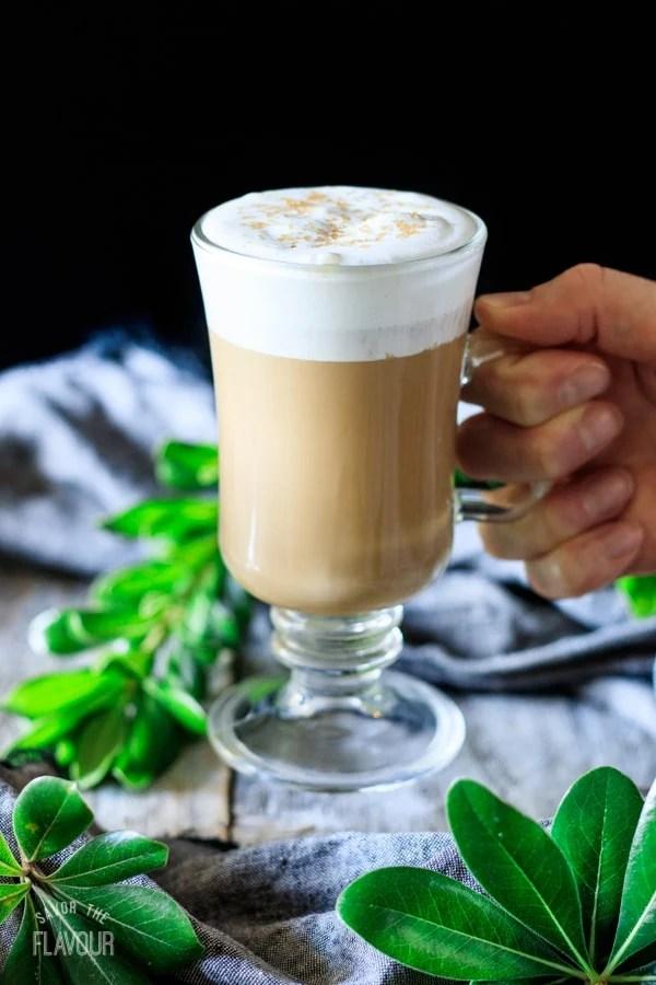 holding a glass of smoked butterscotch latte