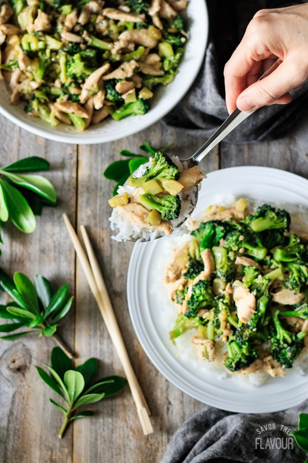 holding a spoonful of chicken and broccoli stir fry
