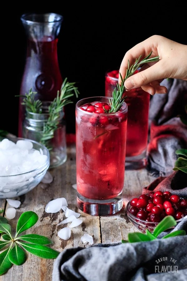garnishing a sparkling cranberry mocktail with rosemary