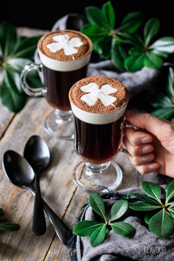 holding a glass of non alcoholic Irish coffee