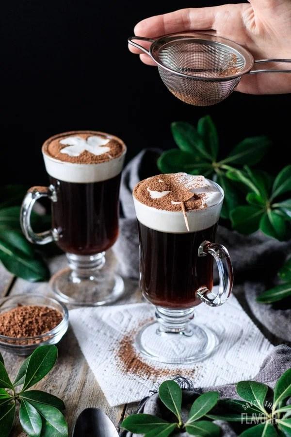 sifting cocoa powder on top of non alcoholic Irish coffee