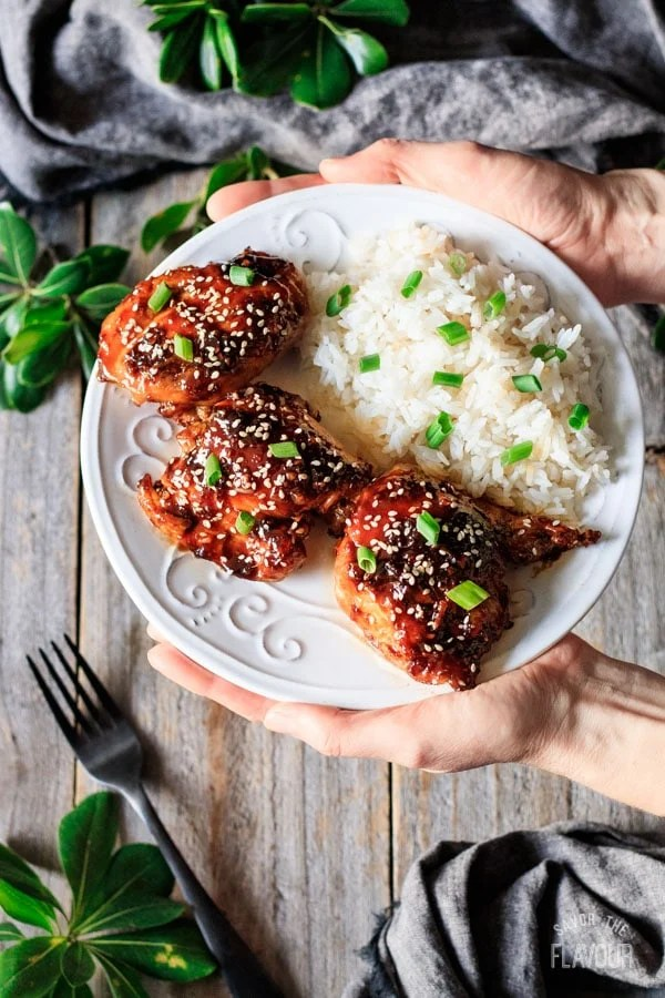 holding a plate of Asian chicken thighs and rice