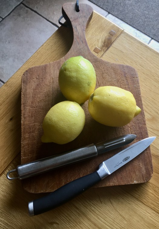 Three lovely, yellow, fresh lemons ready for peeling and slicing