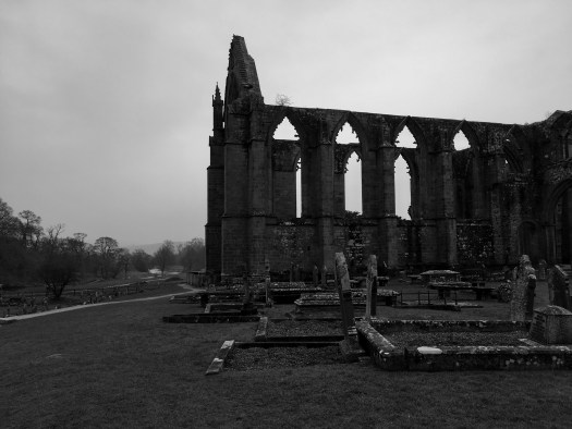 A black and white image of the ruins and grounds of Bolton Abbey