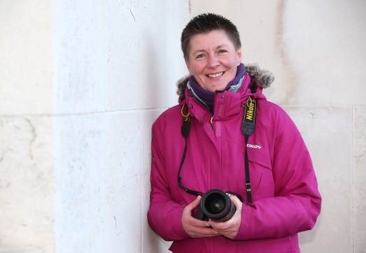 This is Tracey Whitefoot. she is wearing a pink coat and is holding her camera. It is taken at the Victoria Embankment, Nottingham by Joseph Raynor.