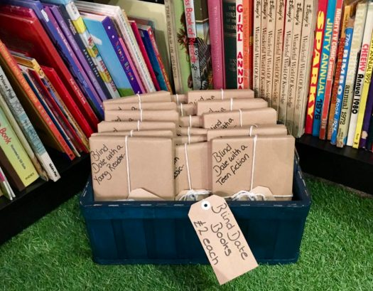 A box contains brown-paper wrapped books a cryptic message on the front, a pot luck blind date with a book