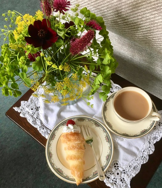 All set for afternoon tea with fresh flowers a cup of tea and an apple cram horn