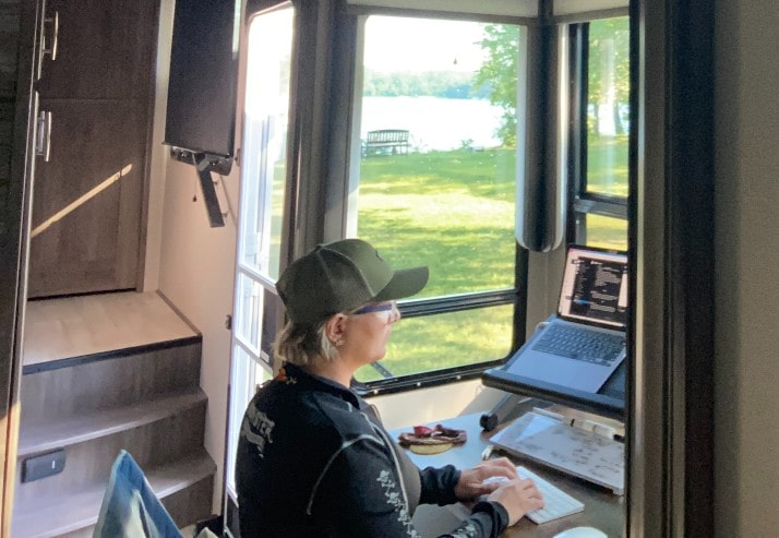 Image of Amy working at her computer in the camper using reliable internet