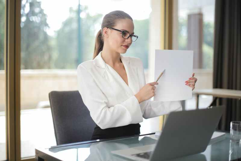 confident businesswoman sharing information from documents in workplace