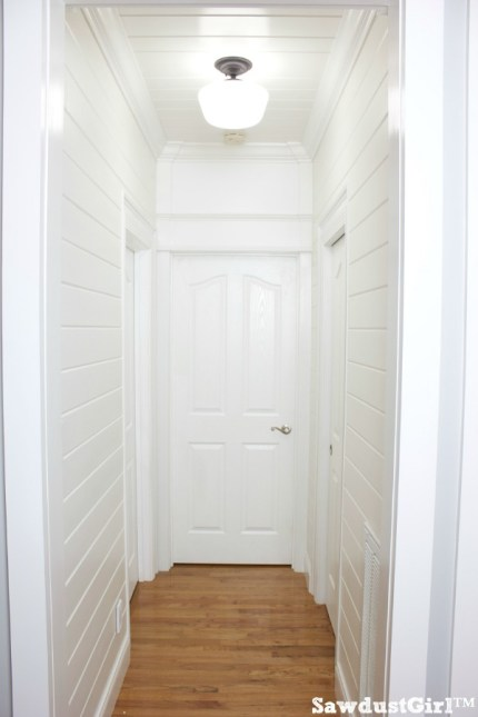 Hallway trim moulding and white plank walls