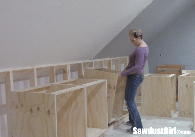 Building a new wall behind cabinets to position them correctly in the room.