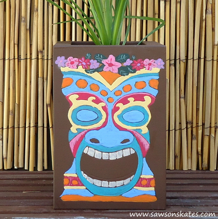 dLove this colorful DIY tiki planter! The plan is so easy to follow, it's made with scrap wood and the tiki faces were traced on the container, so painting them is nearly goof proof! Definitely making this!
