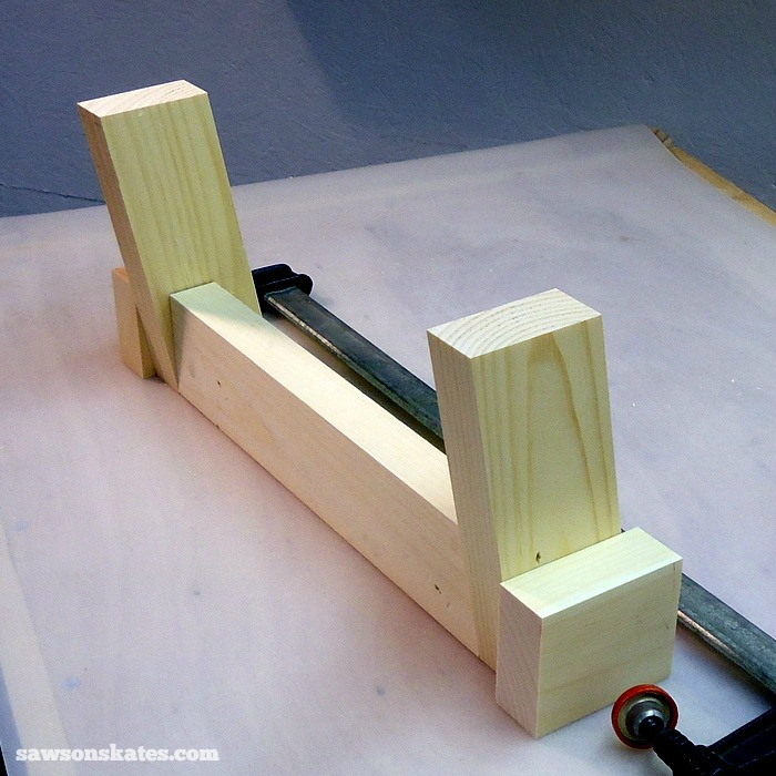 Apply glue to the ends of the Retro Nightstand short stretcher and place on your workbench. Place a leg on each side so that the legs are pointing towards you.