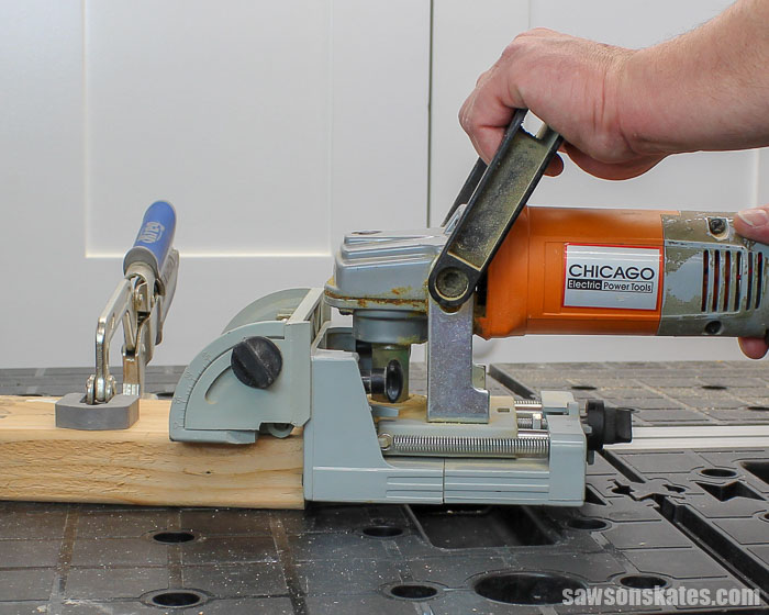 A biscuit joiner cutting a biscuit slot into the endgrain of a workpiece