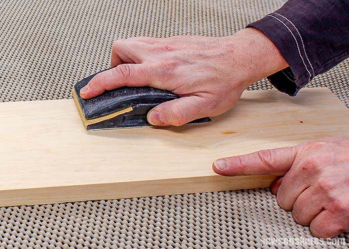 Sanding with the grain of the wood means sanding along the length of the board.