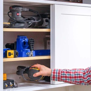 Putting a pair of ear muffs in the DIY workshop storage cabinet