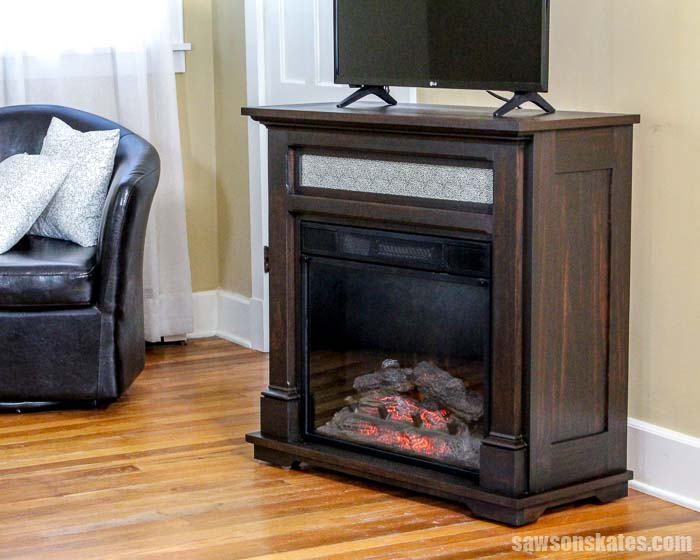 These free plans show how to make a DIY electric fireplace TV stand! Build a surround for your fireplace insert then sit beside a cozy faux fire and watch TV!