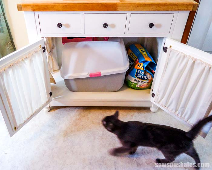 Kitty litter box furniture hides a litter box and has storage for extra litter