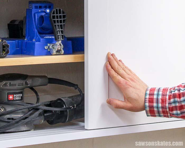 Closing the sliding door of a DIY workshop cabinet