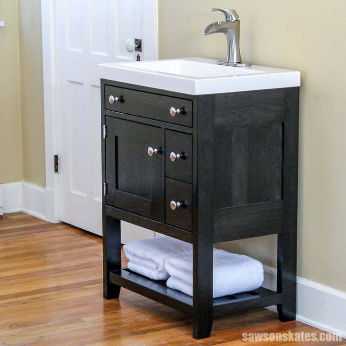Build a modern DIY bathroom vanity with these free plans! The vanity features a charred wood finish, a shelf for towels, and a hidden toilet paper holder!