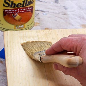 Applying shellac to a piece of wood with a brush