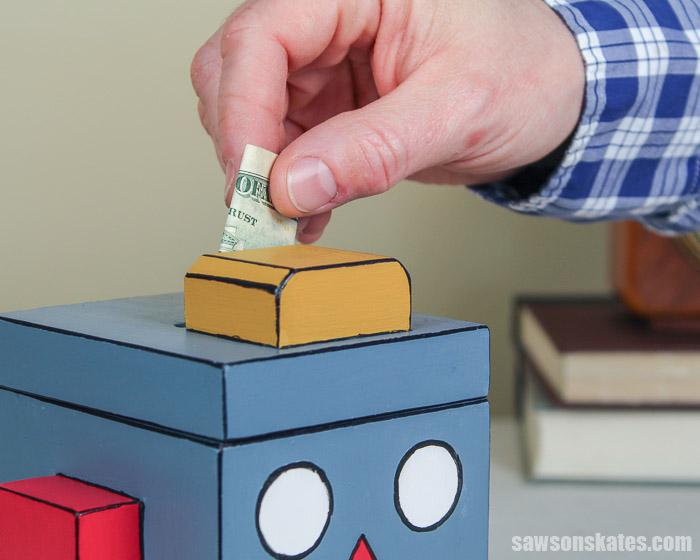 Adding money to an easy to make DIY piggy bank