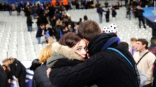 Spectators embrace each other as they stand on the playing field of the Stade de France stadium at the end of a soccer match between France and Germany in Saint-Denis, outside Paris, on November 13.