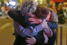 People hugging on the street near the Bataclan concert hall following fatal attacks in Paris, France, on Nov 14, 2015. PHOTO: REUTERS