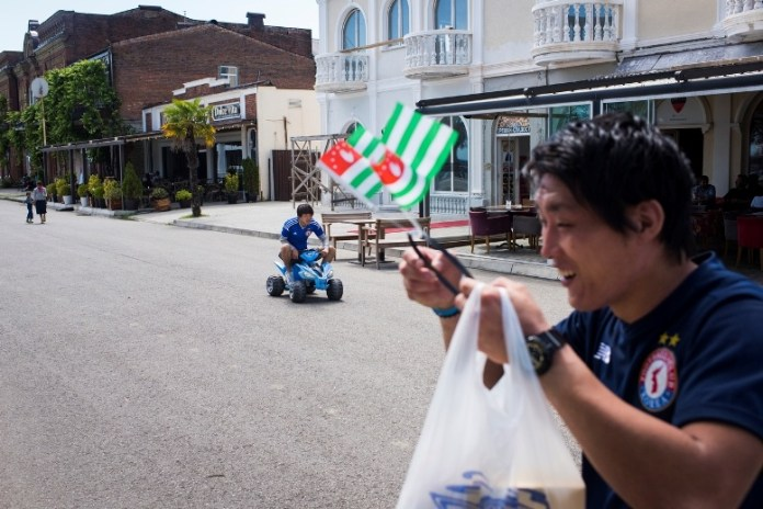 United Koreans in Japan goalkeeper Jae Gun Ri dons an Abkhaz flag headband after a shopping trip to a souvenir shop as his teammate Jang Hwi Jeong rides a bigwheel toy car on June 5, 2016 in Sukhumi, Abkhazia. (Pete Kiehart for ESPN)