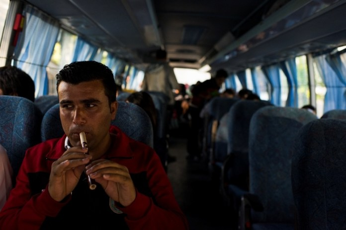 Karwan Mantk, of the Kurdistan team, plays a traditional flute-like instrument called a shimshal while waiting to depart to the final match between Abkhazia and Panjab on June 5, 2016 in Sukhumi, Abkhazia. (Pete Kiehart for ESPN)