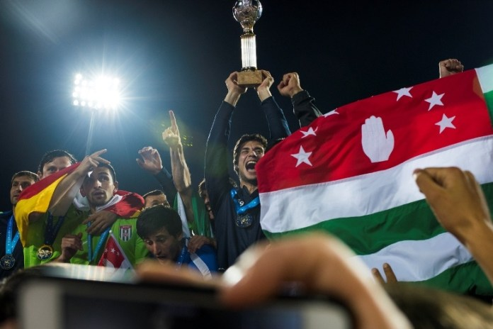 Georgiy Zhanaa hoists the CONIFA trophy after Abkhazia defeated Panjab in the CONIFA Final on June 5, 2016 in Sukhumi, Abkhazia. At left, several of Zhanaa's teammates don a South Ossetian flag in a show of solidarity with Georgia's other separatist republic. (Pete Kiehart for ESPN)