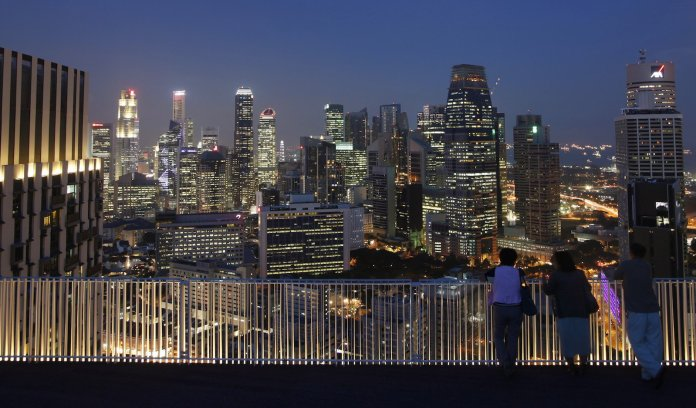 People look at the skyline of the central business district from the Skybridge of The Pinnacles at Duxton public housing estate in Singapore April 25, 2013. REUTERS/Edgar Su