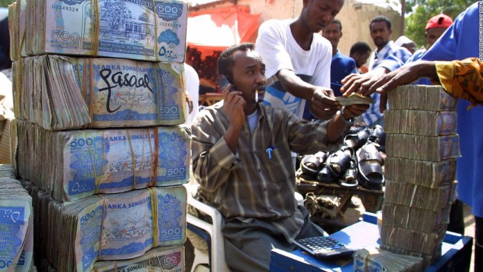 Photos: New member in family of nations? Somali money changer next to piles of banknotes on a busy street in Hargeisa.