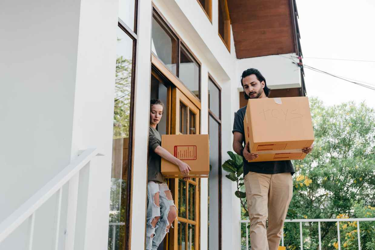 couple carrying carton boxes while moving out of old home